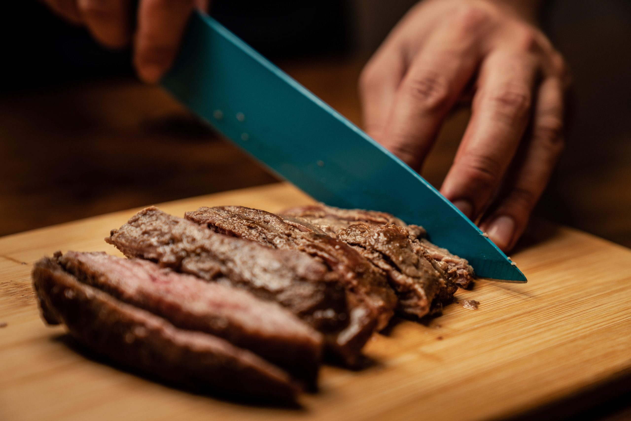 man cutting meat with knif